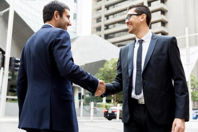 two businessmen shaking hands outside